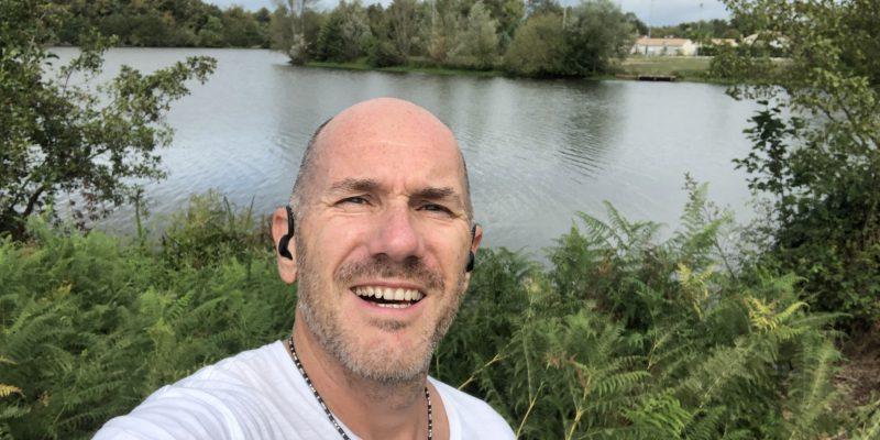 Edmond Tourriol avec ses écouteurs blue-tooth pendant une séance de course à pied devant un lac à Izon.